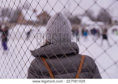 A Woman In A Hat Stands Behind Her Fence At The Rink