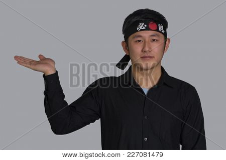 Asian cook show empty hand wearing black bandana with Chinese word traduction ( Victory )