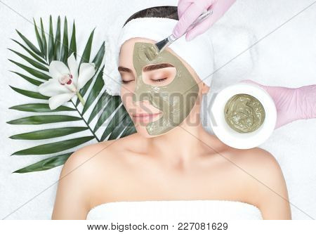 The cosmetologist makes the procedure Microdermabrasion of the facial skin of a beautiful, young woman in a beauty salon.Cosmetology and professional skin care. poster