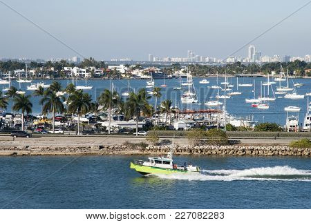 The View Of A Motorboat Passing By Along Macarthur Causeway With Miami Beach Skyline Ina Background