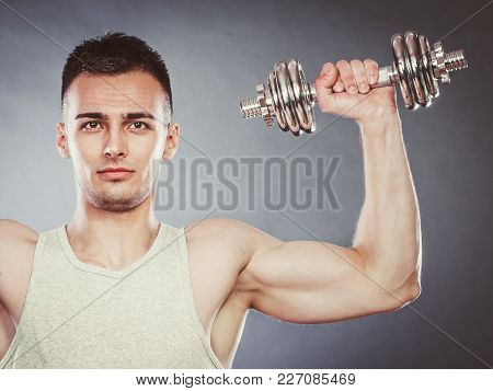 Bodybuilding. Strong Fit Man Exercising With Dumbbell. Muscular Young Guy Lifting Weights Dark Gray