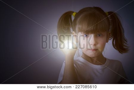 Child In The Dark With A Flashlight