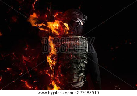 Photo Of A Swat Soldier`s Back With Flame Effect On Black Background.