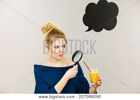 Blonde Woman Holding Magnifying Glass Investigating And Looking Closely At Glass With Orange Juice,