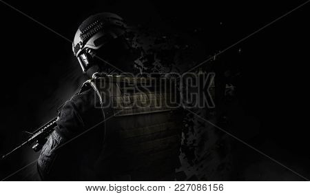 Black and white swat soldier back view posing with dissolving effect on black background. poster