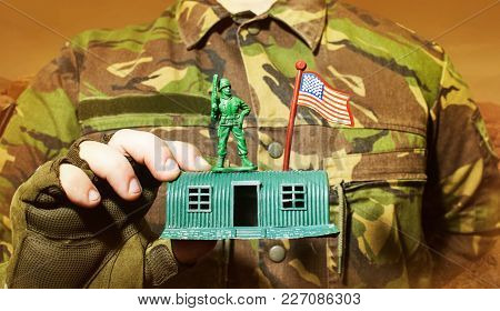 Photo Of A Military Man In Camouflage Jacket Holding A Soldier Toy Standing On Barracks.