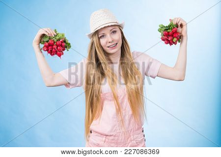 Positive Teenage Blonde Long Hair Girl Wearing Summer Clothing Sun Hat Holding Two Bunches Of Fresh