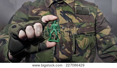 Photo Of A Military Man In Camouflage Jacket Holding A Soldier Toy.