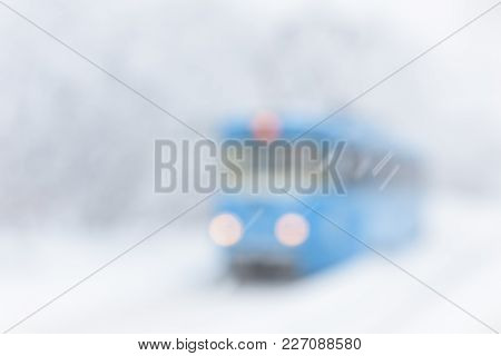 Winter Street Blurred Background. Tram Goes Along The Street During Snowstorm At Winter In Moscow, R