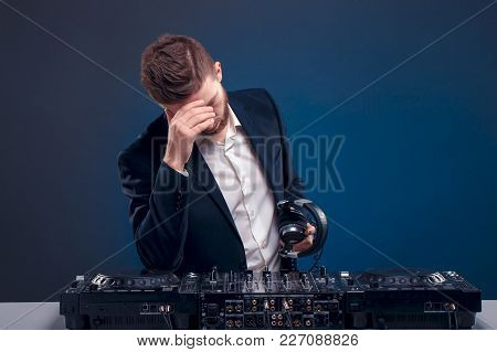 Closeup Portrait Of Confident Dj With Stylish Hair Style And Headphones On Neck Mixing Music On Mixe