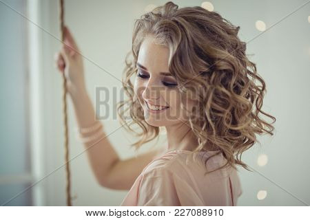Studio Portrait Of Pretty Woman With Curly Hair In 30-th Years Style
