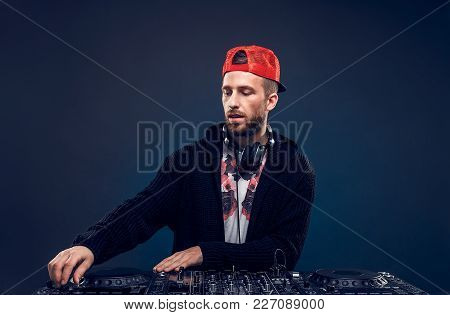 Closeup Portrait Of Confident Dj With Stylish Red Cap And Headphones On Neck Mixing Music On Mixer L