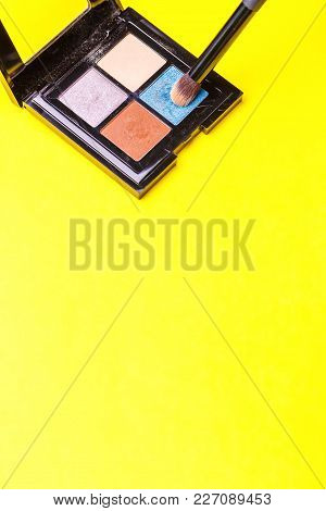 Brush For Make-up Over A Set Of Eye Shadow On Yellow Background. Copy Space