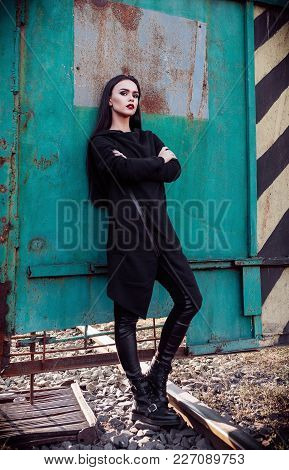 Fashion Shot: Portrait Of The Cute Rock Girl (informal Model) In Tunic And Leather Pants Standing In