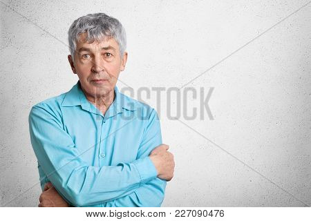 Indoor Shot Of Confident Mature Man In Formal Shirt, Keeps Hands Crossed, Looks Directly Into Camera