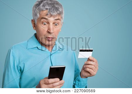 Shocked Grey Haired Male Looks With Frustrated Expression At Smart Phone, Can`t Understand How Use M