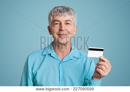 Pleased Mature Male With Cheerful Expression In Formal Shirt, Holds Credit Plastic Card, Happy To Ge