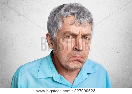 Displesed Unhappy Wrinkled Mature Male Frowns Face And Curves Lips, Wears Formal Shirt, Poses Agains