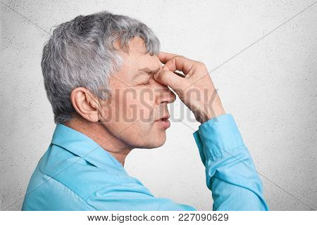 Profile Of Exhausted Grey Haired Male In Formal Shirt, Keepd Hands On Nose, Poses Against White Conc