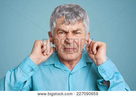 Portrait Of Upset Annoyed Mature Man Plugs Ears With Fingers, Dressed In Formal Shirt, Poses Against