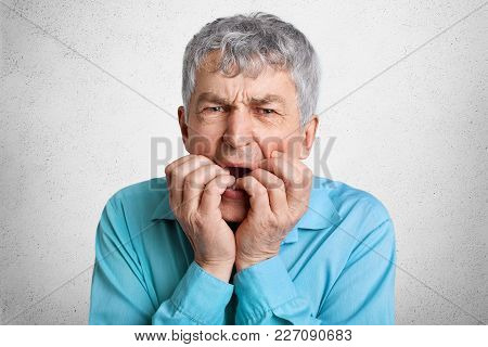Elderly Puzzled Male With Grey Hair Feels Uncertain About Something, Shrugs Shoulders, Dressed In Fr