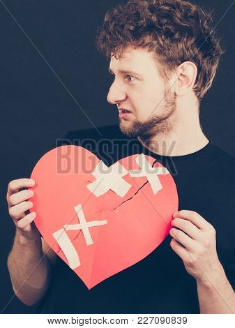 Separation And Conflict. Young Upset Sad Man With Red Heart Glued By Plaster. Guy Lost His Love Rela