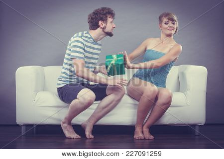 Couple Sitting On Couch At Home. Young Man Giving Offended Woman Gift Box, Girl Refusing To Accept P
