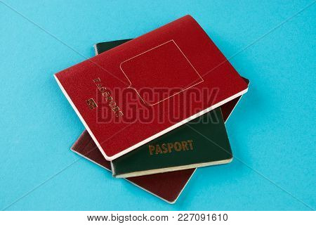 Passport Travel Document. Red, Green And Brown Passports On Blue Background With Copy Space, View Fr