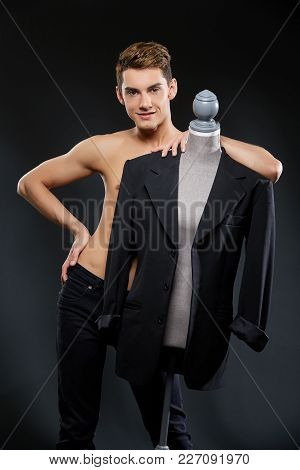 Handsome Young Man Wearing Black Jacket Over Naked Torso. Studio Shot On Dark Background. Copy Space