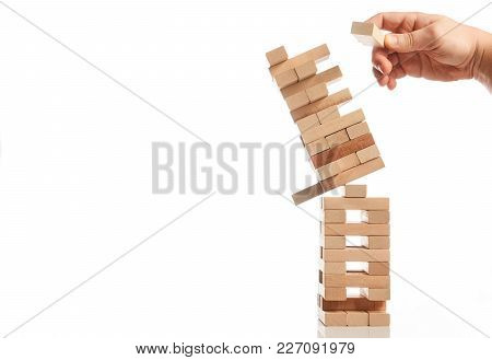 Businessman Hand Take One Block From Tower Of Wooden Blocks And Tower Collapses On White Background