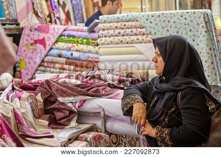 Tehran, Iran - April 29, 2017: Iranian Woman In Religious Veil Is Looking For Fabrics In A Store Wit