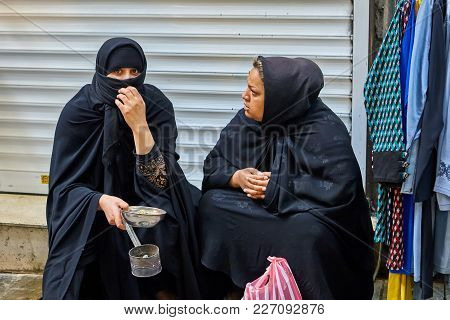 Tehran, Iran - April 29, 2017: Two Iranian Women In Hijabs Are Sitting On The Market, One Of Them Co