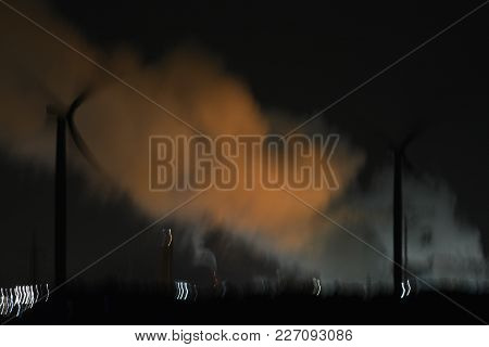 A burry image taken at night time of a fractionation plant using there plants lights to light up the sky through the steam also be generated by the plant. In foreground burry image of two windmills silhouetting using the light from the plant be hide