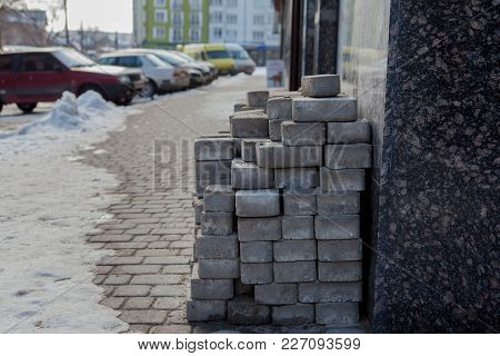 Piled Up Bricks On A Newly Paved Parking Area.