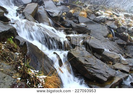 Waterfall Flowing Among The Huge Stones. Mountain River. Water In The Mountains