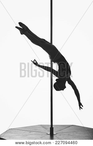 Beautiful Fit Pole Dancer Girl Silhouette. Young Woman Making Figures On Pylon. Studio Shot Isolated