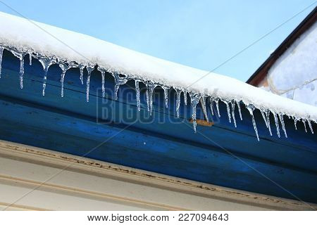 Icicles Hang Down From Under The Roof Of The House. Frozen Winter Pattern In The Row
