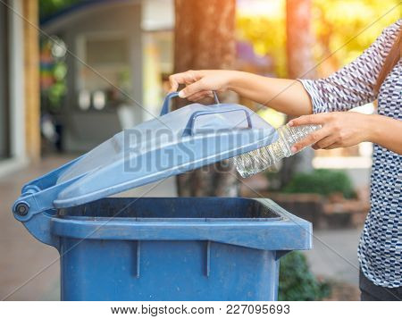 Closeup Portrait Woman Hand Throwing Empty Plastic Water Bottle In Recycling Bin.