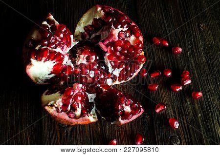 Open Fresh Ripe Pomegranates On Wooden Background.