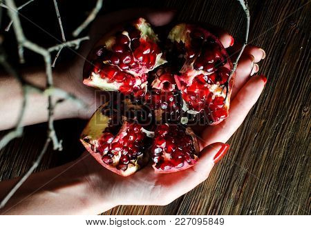 Open Fresh Ripe Pomegranates In Female Hands On A Wooden Background.