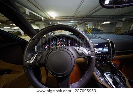 Interior of modern car cabin, focus on steering wheel.