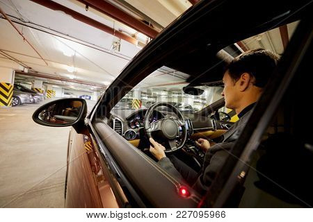 Man sits on driver seat in modern car at underground parking.