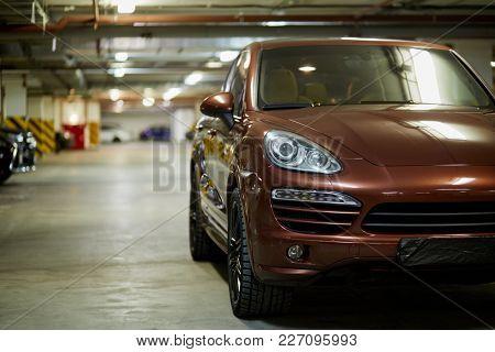 New brown sports car, standing at underground parking.