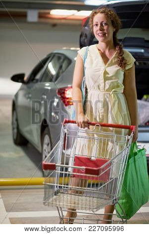 Young smiling woman with bag and shopping cart at underground parking.