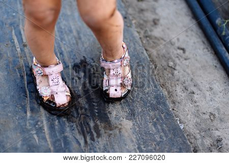 Child In Mud Pink Sandals In The Summer On The Street