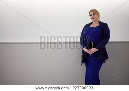 Portrait of blond woman in blue dress and shawl with handbag near wall.