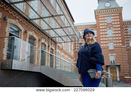 Smiling blonde woman in blue suit and hat stands in inner yard of house of red brick.