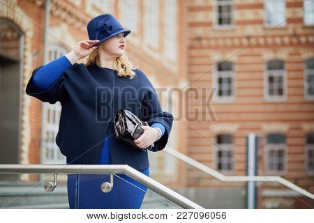 Blonde woman in blue suit and hat stands on stairs in inner yard of house of red brick.