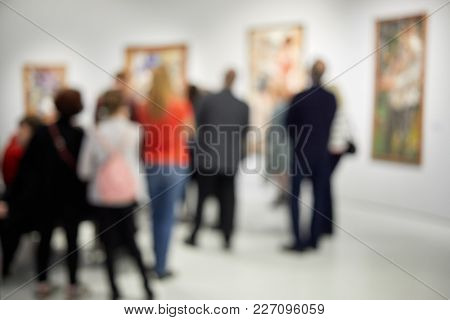 Group of people look at paintings in museum, blurred image.