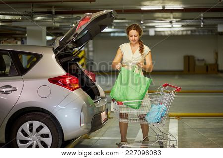 Young woman moves bags from shopping cart to trunk of car at underground parking.